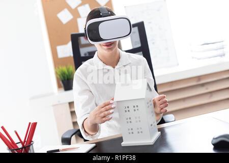 Junges Mädchen sitzt in der virtuellen Realität Gläser. Vor ihr auf dem Tisch ist die Aufteilung des Hauses. - Stockfoto