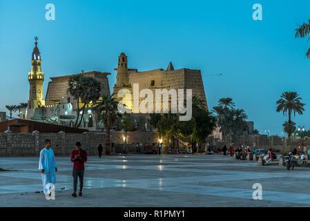 Menschen zu Fuß auf dem Platz vor der alten illuminierten Luxor-Tempel bei Nacht mit dunkelblauen Himmel und glühende brickwalls, Luxor, Ägypten, octob - Stockfoto