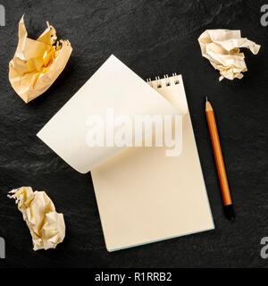 Brainstorming eine Idee. Ein Foto von einer Spirale Notizblock mit einem leeren Blatt Papier und Zerknitterte Seiten, geschossen von oben auf einem schwarzen Hintergrund w - Stockfoto