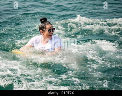 Eine junge Frau, Mädchen, kühlt sich ab im Meer schwimmen mit einem inflateble Bananne - Stockfoto