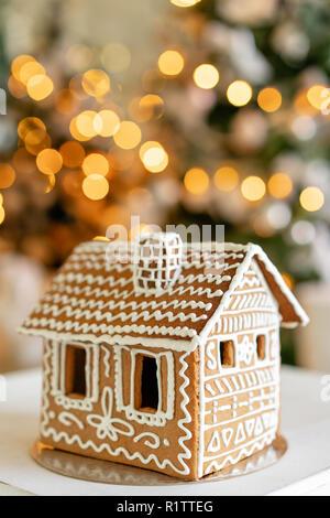 Lebkuchenhaus auf Tisch. Defokussierten Lichter des Weihnachtsbaums. Morgen im hellen Wohnzimmer. Urlaubsstimmung.