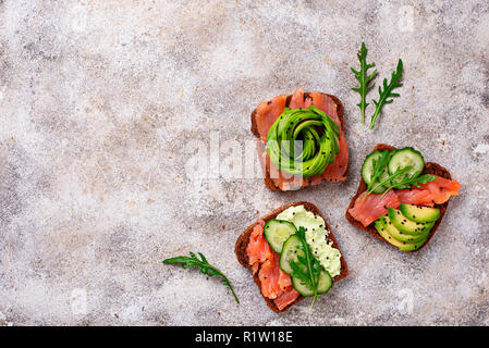 Avocado Toast mit Lachs auf Roggenbrot - Stockfoto