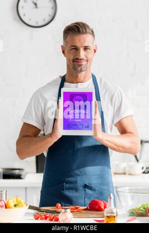 Mann mit digitalen Tablet mit Online shopping Illustration an Küche - Stockfoto