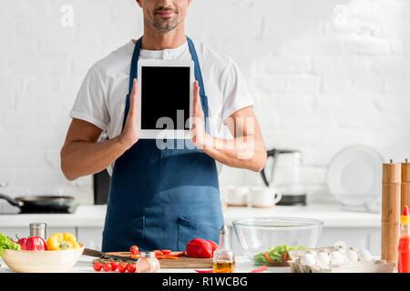 Mann in Schürze mit digitalen Tablet in der Hand in der Küche - Stockfoto