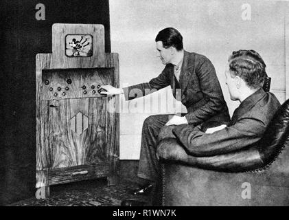 Ein 1935 Foto, die frühen Tage des Fernsehens in Großbritannien - zwei Männer in Anzügen sitzen zu sehen Micky Maus spielt Dudelsack auf dem kleinen Fernseher in einem großen Holzgehäuse untergebracht - Stockfoto