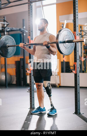 Muskulöse junge Sportler mit künstlichen Bein arbeiten mit Langhantel im Fitnessstudio - Stockfoto