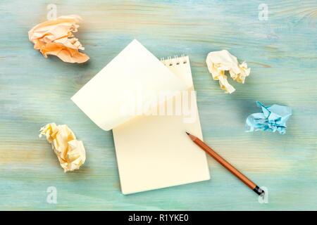 Auf der Suche nach Inspiration. Ein Foto von einer Spirale Notizblock mit einem leeren Blatt Papier und Zerknitterte Seiten, geschossen von oben auf eine hellblaue Hinterg - Stockfoto