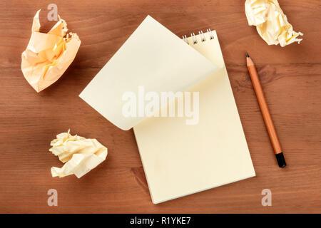 Idee Krise. Ein Foto von einer Spirale Notizblock mit einem leeren Blatt Papier und Zerknitterte Seiten, geschossen von oben auf einem dunklen Hintergrund mit einem - Stockfoto