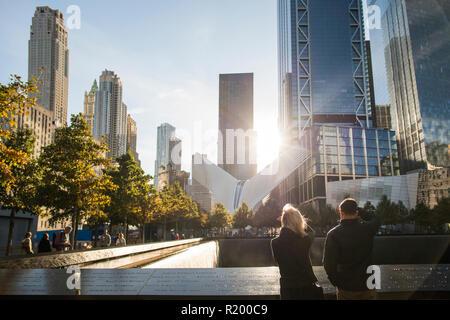 NEW YORK - USA - 28. Oktober 2017. Ein paar steht vor dem Ground Zero Memorial in Manhattan. - Stockfoto