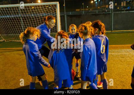 Fußball-Trainer und Mädchen Fußball Mannschaft in Unordnung auf dem Feld in der Nacht - Stockfoto