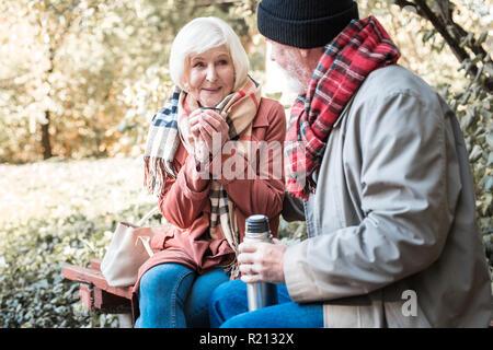 Freudige nette Frau hält eine Tasse mit heißem Tee - Stockfoto