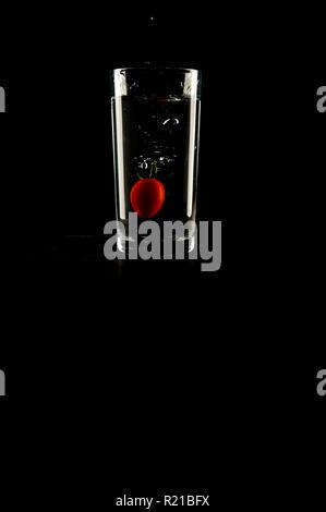 Ein Baby tomato planschen in einem Glas Wasser auf schwarzem Hintergrund - Stockfoto