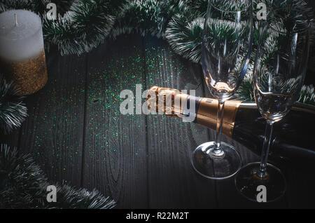 Eine Flasche Champagner und zwei Gläser stehen auf einem dunklen Grau Holztisch von Weihnachtsschmuck und einer weiß-gold Kerze steht neben es umgeben. - Stockfoto