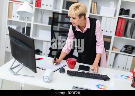 Ein junges Mädchen steht in der Nähe des Schreibtisch im Büro und Tippen auf der Tastatur. - Stockfoto