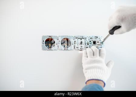 Nahaufnahme von einem Elektriker Montage Steckdosen auf der weißen Wand - Stockfoto