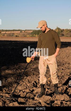 Militärische sapper mit einem Metalldetektor untersucht die Erde im Feld für das Vorhandensein von Minen - Stockfoto