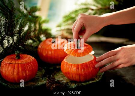Handgefertigte Keramik in Form von kürbisse. Weihnachten Pfoten. Die Atmosphäre der Feier und Wohnkomfort. Hände öffnen Sie den Deckel auf den Topf. - Stockfoto