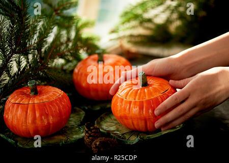 Handgefertigte Keramik in Form von kürbisse. Weihnachten Pfoten. Die Atmosphäre der Feier und Wohnkomfort. Hände gewickelt um einen warmen Topf Essen - Stockfoto