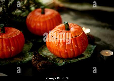 Handgefertigte Keramik in Form von Kürbissen. Weihnachten Pfoten. Die Atmosphäre der Feier und Wohnkomfort. Fröhliches orange Töpfe an den Ofen und Braten - Stockfoto