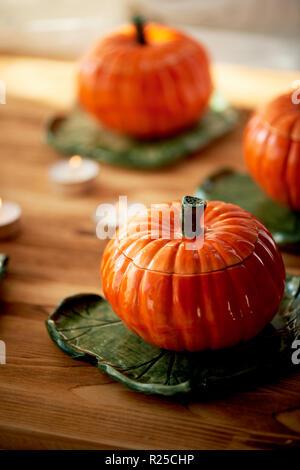 Handgefertigte Keramik in Form von Kürbissen. Die Atmosphäre der Feier und Wohnkomfort. Fröhliches orange Töpfe auf dem Herd und Braten. Kürbis Brei - Stockfoto