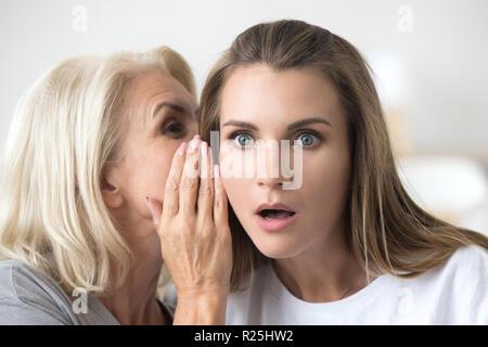 Ältere Mutter Flüstern in jungen Tochter Ohr sagen schockierend n - Stockfoto