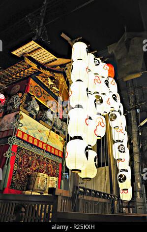 KYOTO, Japan - 15. JULI 2011: Einen tragbaren Schrein in Rot und Gold bestickten Tuch und glühenden Papierlaternen befestigt - Stockfoto