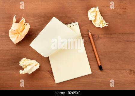 Auf der Suche nach Ideen. Ein Foto von einer Spirale Notizblock mit einem leeren Blatt Papier und Zerknitterte Seiten, geschossen von oben auf einen hölzernen Hintergrund mit einem scharfen - Stockfoto