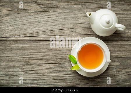 Tasse grün und Kräuter Tee serviert mit Kaffee Topf auf hölzernen Tisch - Stockfoto