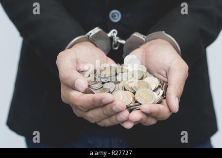 Mann die Hände in Handschellen mit Thai Münzen. verhaftung Geld konzeptionelle stehlen.