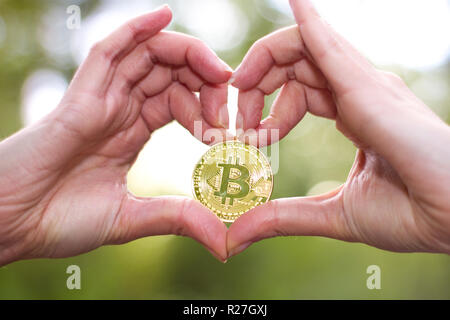 Weibliche Hände in Herzform mit einem bitcoin oder cryptocurrency mit grünem Hintergrund - Stockfoto