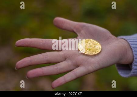 Weibliche offene Hand mit einem bitcoin oder cryptocurrency in der Mitte mit grünem Hintergrund - Stockfoto