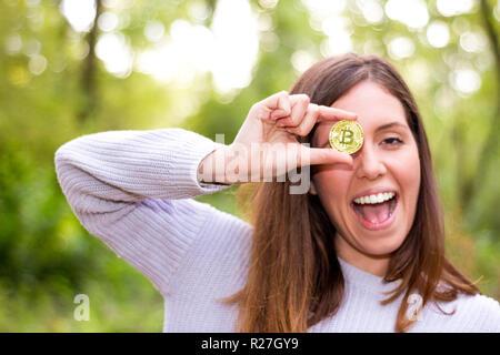 Jungen Kaukasischen europäischen Frau mit einem bitcoin oder cryptocurrency lächelt glücklich Geradeaus schauen mit offenen Mund und perfekte Lächeln - Stockfoto