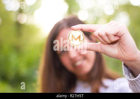 Europäische Kaukasischen jungen Mädchen aus Fokus lächelnd Holding Monero Münze crypto oder fokussiert cryptocurrency - Stockfoto