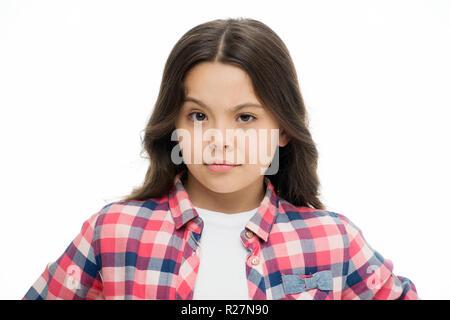 Kleines Mädchen Heben der Augenbrauen isoliert auf Weiss. Zuversichtlich Kind mit langen brünetten Haaren. Friseur Salon für die Entwicklung der Kinder. Hair Fashion und Hautpflege. Fühlen sich unsicher. Schönheit suchen. Lässige Stil. - Stockfoto