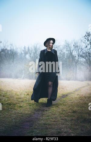 Mädchen in einem Mantel im Nebel - Stockfoto