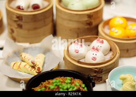 Dim Sum, traditionelle Chinesische Knödel in Bambus steamer, Schwein und Tier Thema für Kinder. Street Food für Kinder in China, Hong Kong. Abendessen mit der Familie wi - Stockfoto