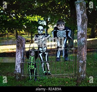 Drei Jungen im Skelett halloween Kostüme hängen an einem alten schmiedeeisernen Tor - Stockfoto