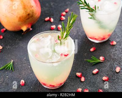 Herbst und Winter cocktails Idee - weiße Sangria mit Rosmarin, pomegrante und Zitronensaft und Zutaten auf schwarzem Zement Hintergrund. - Stockfoto