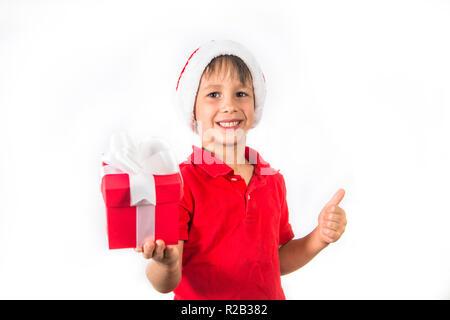 Kind Junge in Weihnachten Santa Hat und Red vorhanden Box auf Weiß. - Stockfoto