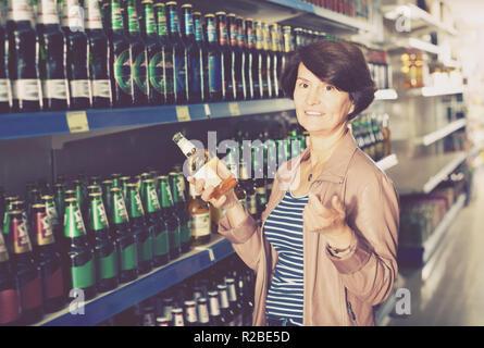 Ältere Frau Auswahl Flasche Bier im Supermarkt - Stockfoto