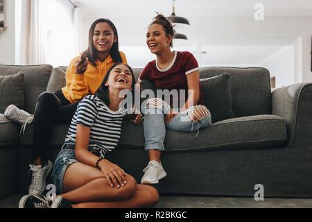Drei junge Mädchen zusammen sitzen zu Hause vor dem Fernseher sitzen und Lachen. Teenage Mädchen an einer sleepover Spaß vor dem Fernseher sitzen im Wohnzimmer - Stockfoto