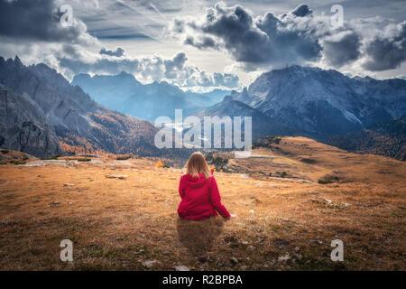 Junge Frau sitzt auf dem Hügel gegen die majestätischen Berge bei Sonnenuntergang im Herbst in den Dolomiten, Italien. Landschaft mit Mädchen, bewölkter Himmel, orange gra - Stockfoto
