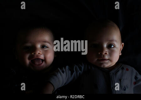 Baby Zwillingsbrüder in der Dunkelheit - Stockfoto