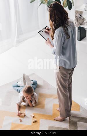 Hohe Betrachtungswinkel der Psychologe mit Zwischenablage in der Nähe von Kind, während sie auf dem Boden und spielen mit Holz unterbauen - Stockfoto