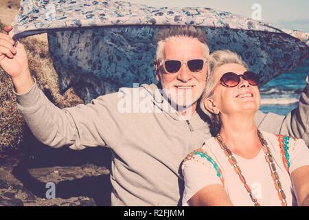 Glückliches Paar der älteren Menschen Herr und Dame sitzen in der Nähe des Ozeans mit hippy farbige Kleidung Stil. Genießen und Spaß mit alternativen Lebensstil haben. Freundliche Kaukasier, genießen die Ferien zusammen - Stockfoto