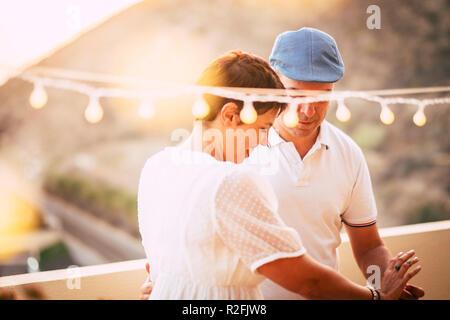 Liebe und romantische kaukasischen mittleren Alter Paar tanzen und zusammen mit Liebe und Romantik auf der Terrasse zu Hause mit Blick bleiben. Sonnenuntergang und erstaunliche Licht im Hintergrund. glückliche Menschen leben genießen - Stockfoto
