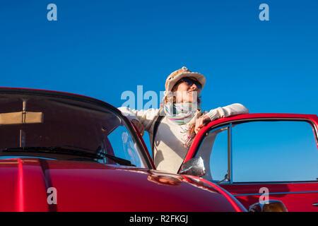40 s Frau hippy Stil genießen das Wetter draußen von ihrem alten roten Auto. Vintage Leben und Stil, blau klar Himmel Hintergrund - Stockfoto
