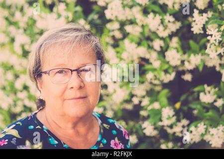 Schöne ältere Frau Porträt mit eyegloass und nett Lächeln, Blick in die Kamera. Natürlichen Blumen defokussiertem Hintergrund und Blumen auf dem Kleid - Stockfoto