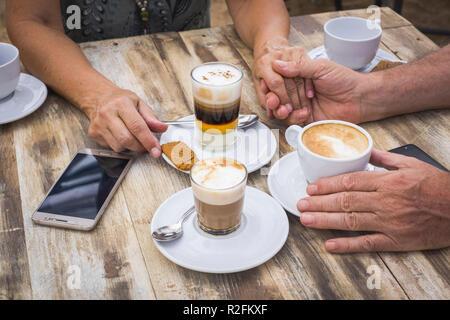 Die Leute trinken Kaffee und Cappuccino an der Bar über einen hölzernen Tisch mit Getränken und Mobilfunktechnik. Geselligkeit und Liebe conept Für erwachsene Mann und Frau andere Freunde warten