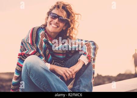 Schöne nette Dame mit Swirl Haar lächelte sie, während Sie in der Nähe des Ozeans sitzen. Poncho und hippy Kleidung Freiheit Konzept darzustellen. Ferienhäuser Stil in magischer Atmosphäre. Fernweh. - Stockfoto